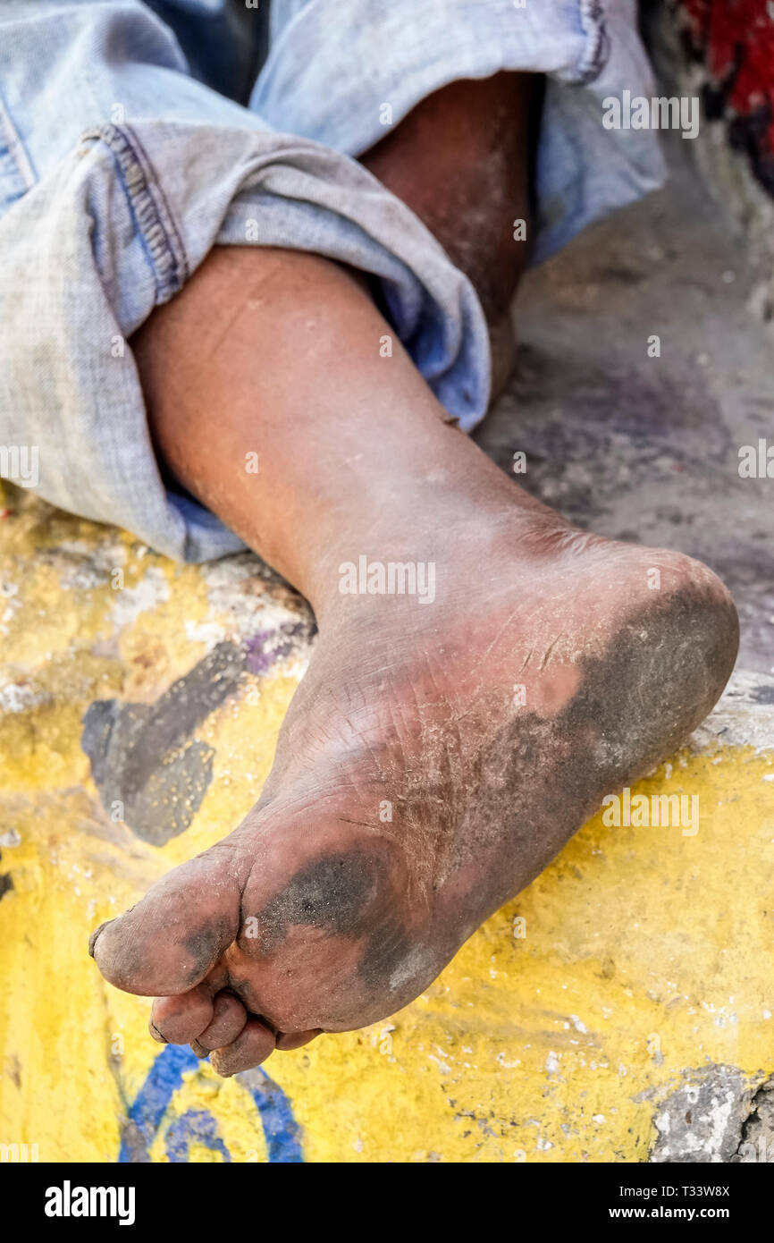 Cartagena Colombia Old Walled City Center centre Getsemani Hispanic resident residents man homeless sleeping street dirty foot feet no shoes shoeless - Stock Image