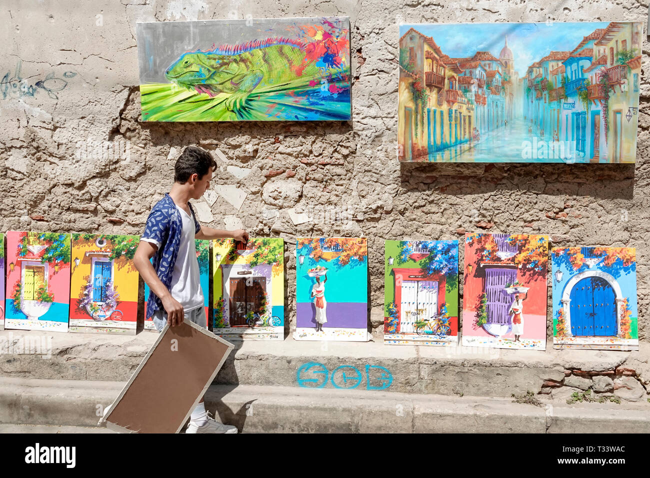 Cartagena Colombia Old Walled City Center centre Getsemani Arte Getsemani display sale art paintings souvenirs Hispanic resident residents man gallery - Stock Image