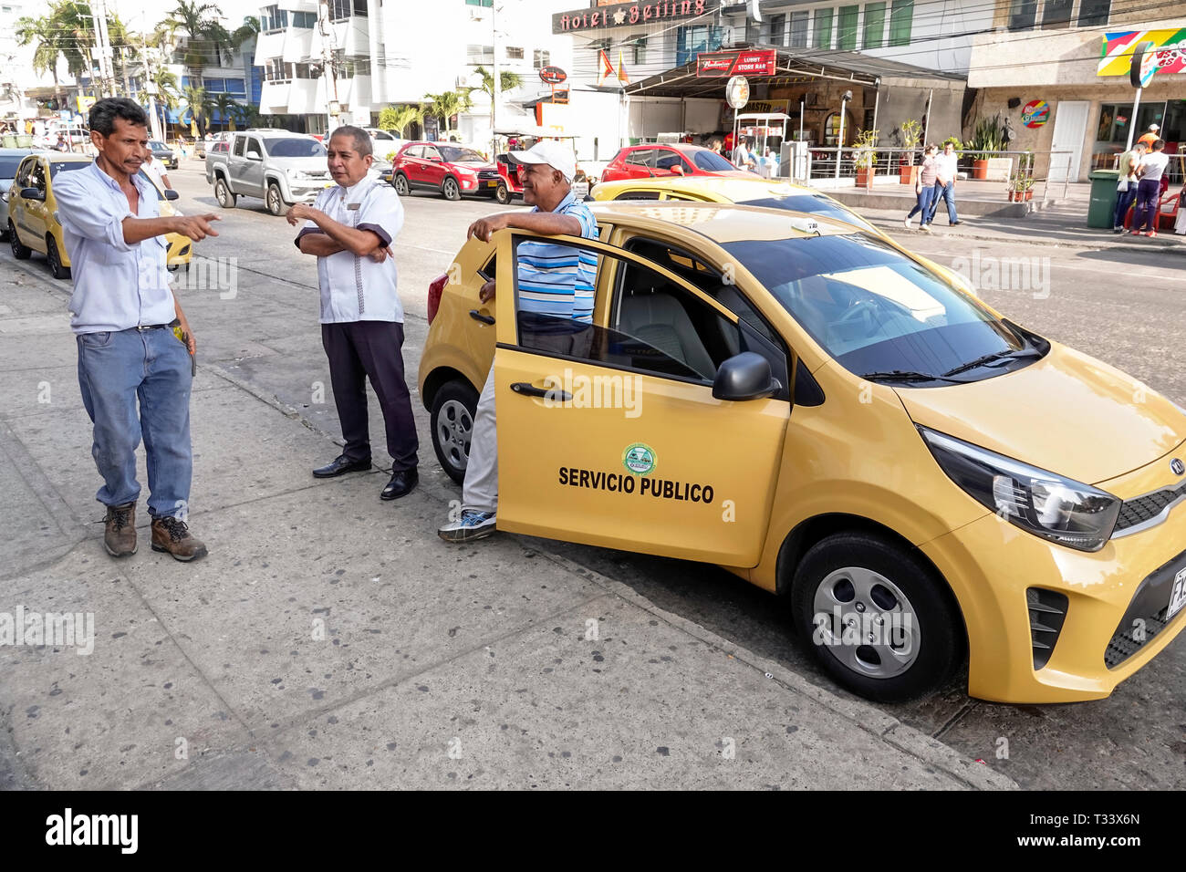 Cartagena Colombia Bocagrande taxi taxis cab cabs driver drivers talking Hispanic resident residents man friends - Stock Image