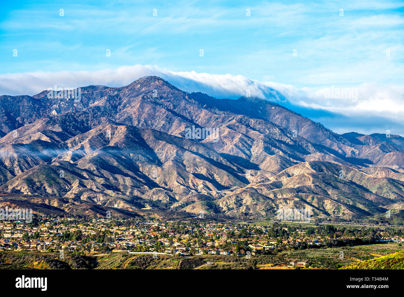 A view of a small city in Lake Elsinore framed against a rugged mountainside. - Stock Image
