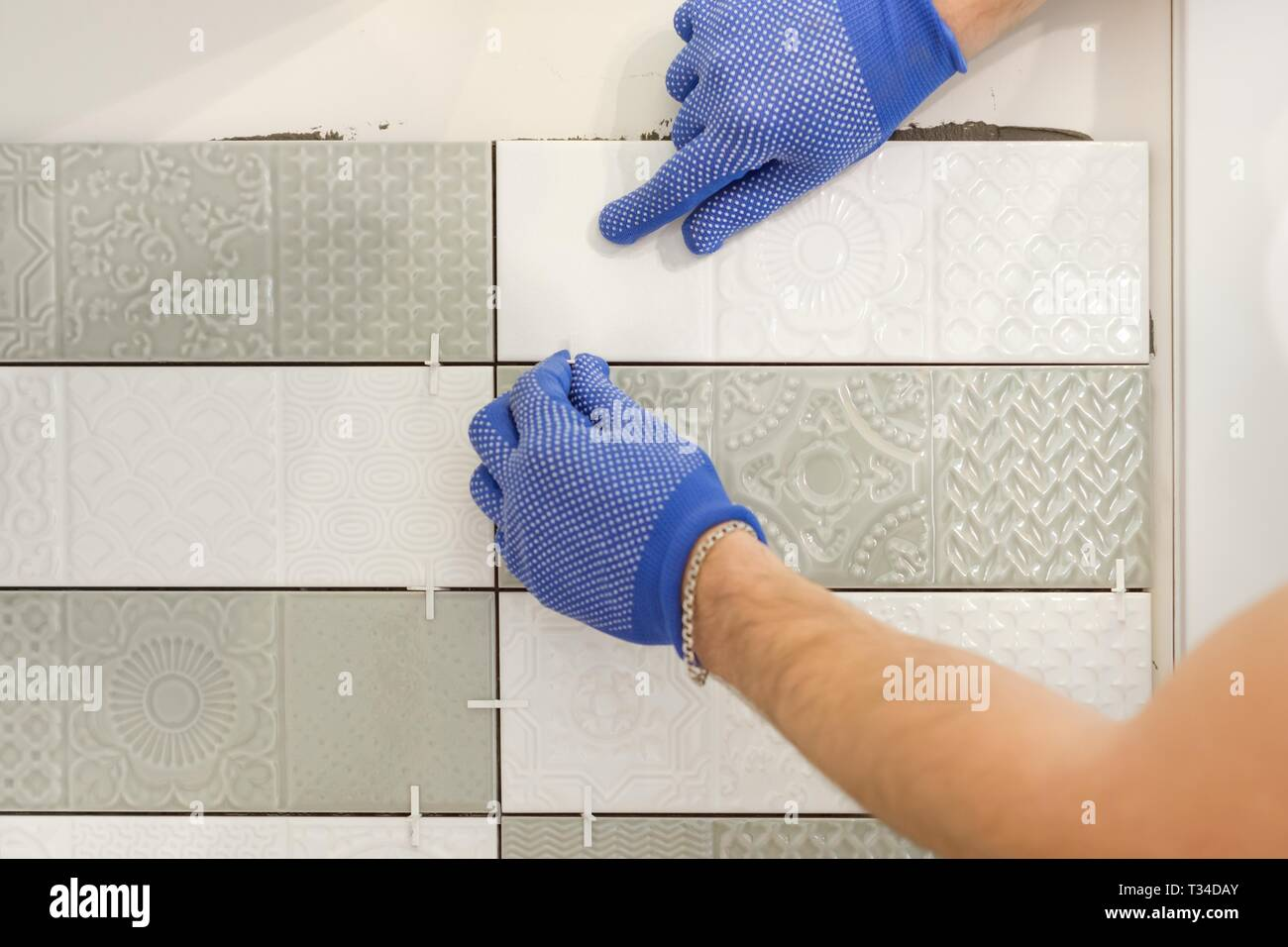 Installing ceramic tiles on the wall in kitchen. Placing tile spacers with hands, renovation, repair, construction. - Stock Image