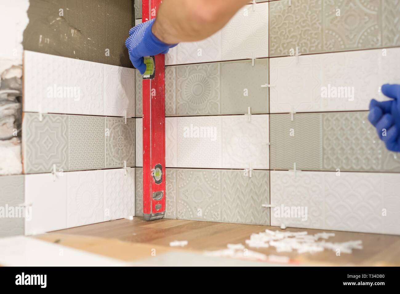 Repair And Construction Of The Kitchen Hands Of Tiler Installing Ceramic Tiles On The Wall Use Professional Tools Real Laying Process Stock Photo Alamy
