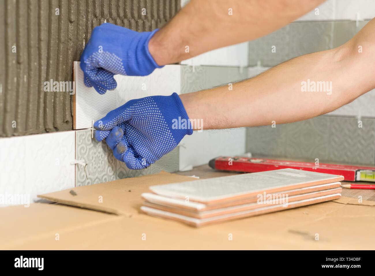 Installing ceramic tiles on the wall in kitchen. Placing tile spacers with hands, renovation, repair, construction - Stock Image