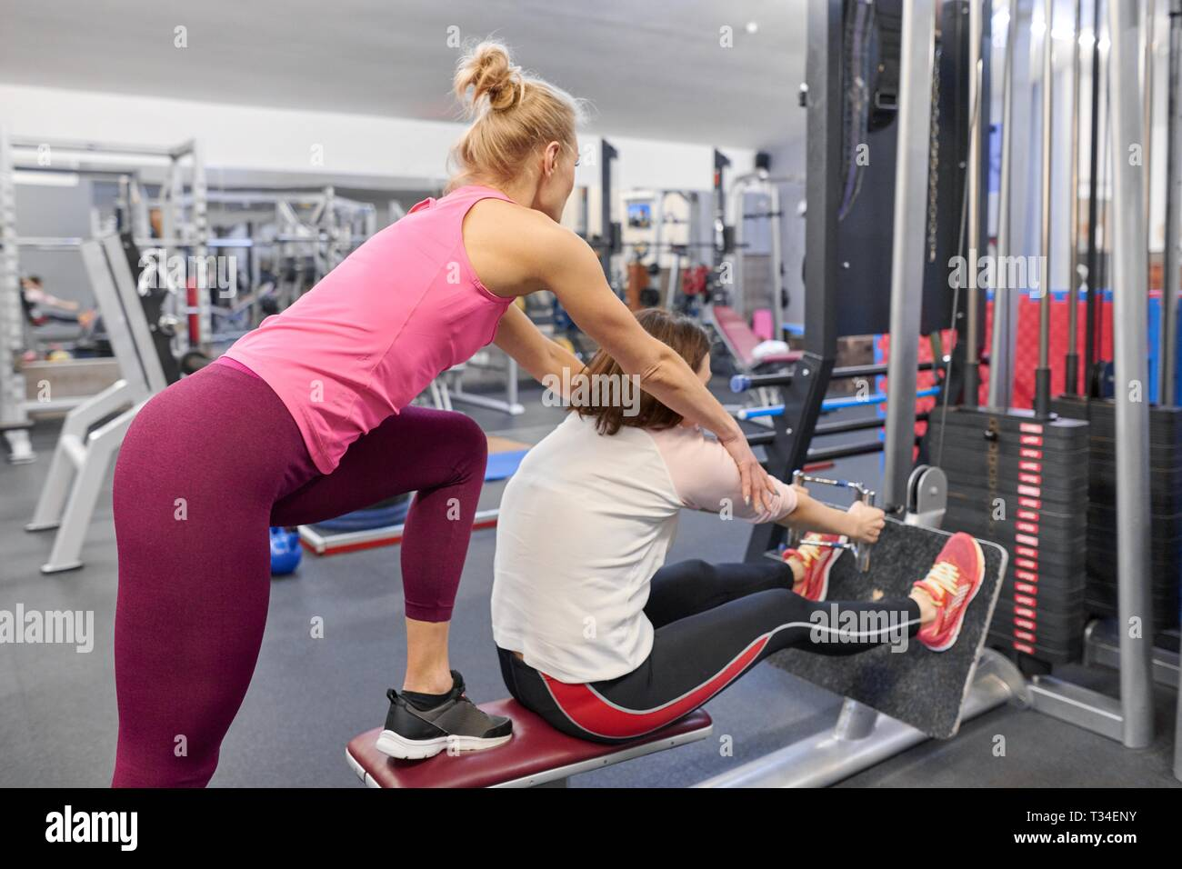 Personal fitness trainer working exercise with mature woman in the gym. Health fitness sport age concept. - Stock Image