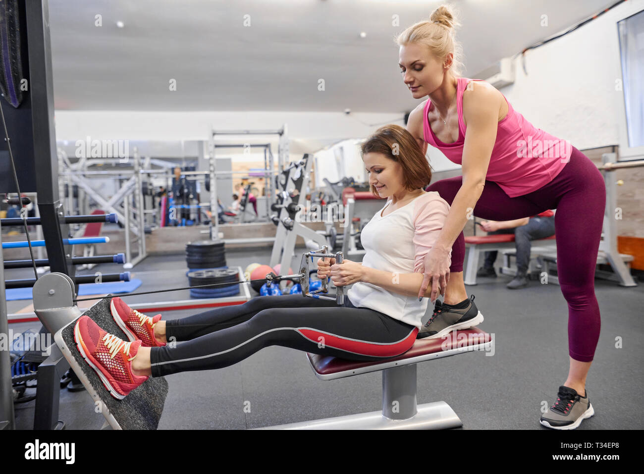 Mature woman doing sport exercises with personal trainer at gym. Female instructor assisting older woman. - Stock Image
