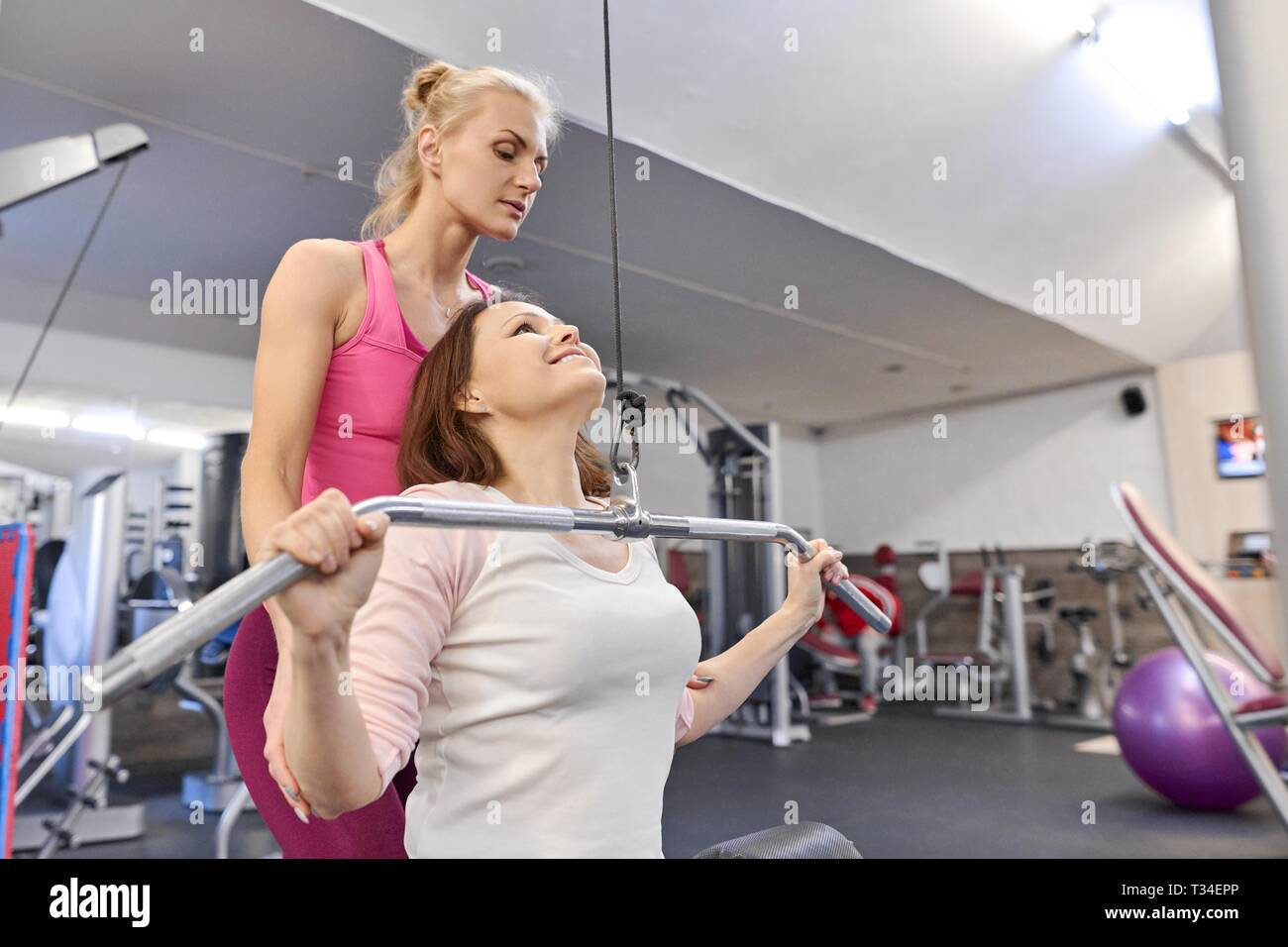 Personal fitness instructor helping summer woman exercising in health club. Health fitness sport age concept. - Stock Image