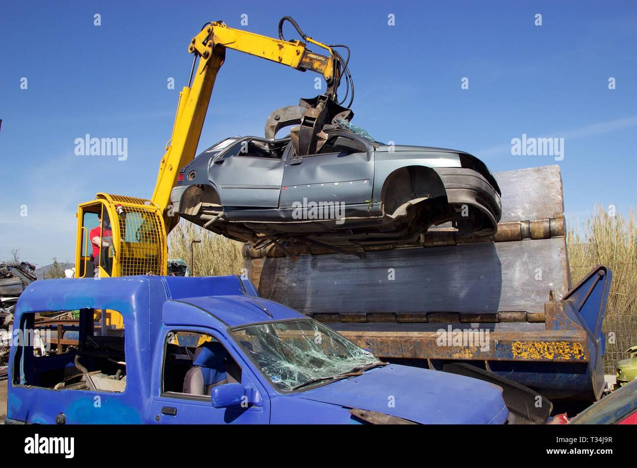 Crane with claw move an old crushed car from junkyard at car press crusher for recycling - Stock Image