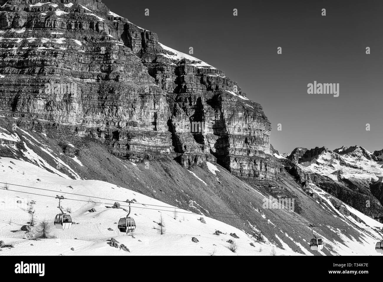 Black and white landscape. Cable car to sky resort. Massive rocks and mountains on the horizon. Winter holidays in the Alps Stock Photo