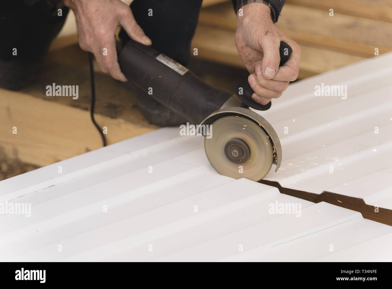 Construction worker sawing steel sheet with trapezoidal profile - Stock Image