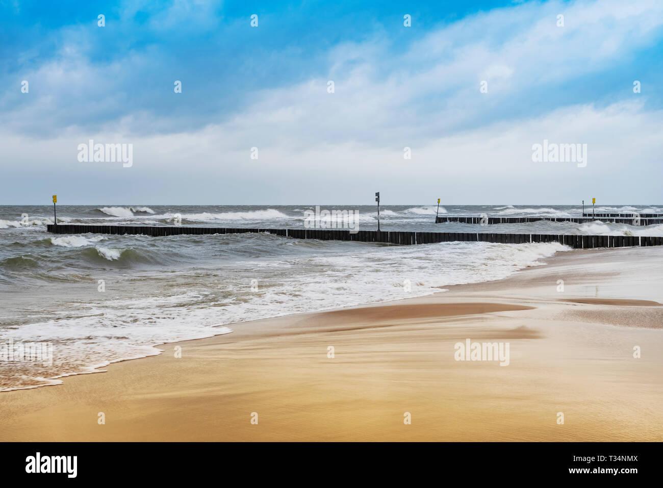 Sandy Beach with groynes on the Baltic Sea, Kolobrzeg, West Pomeranian, Poland, Europe - Stock Image