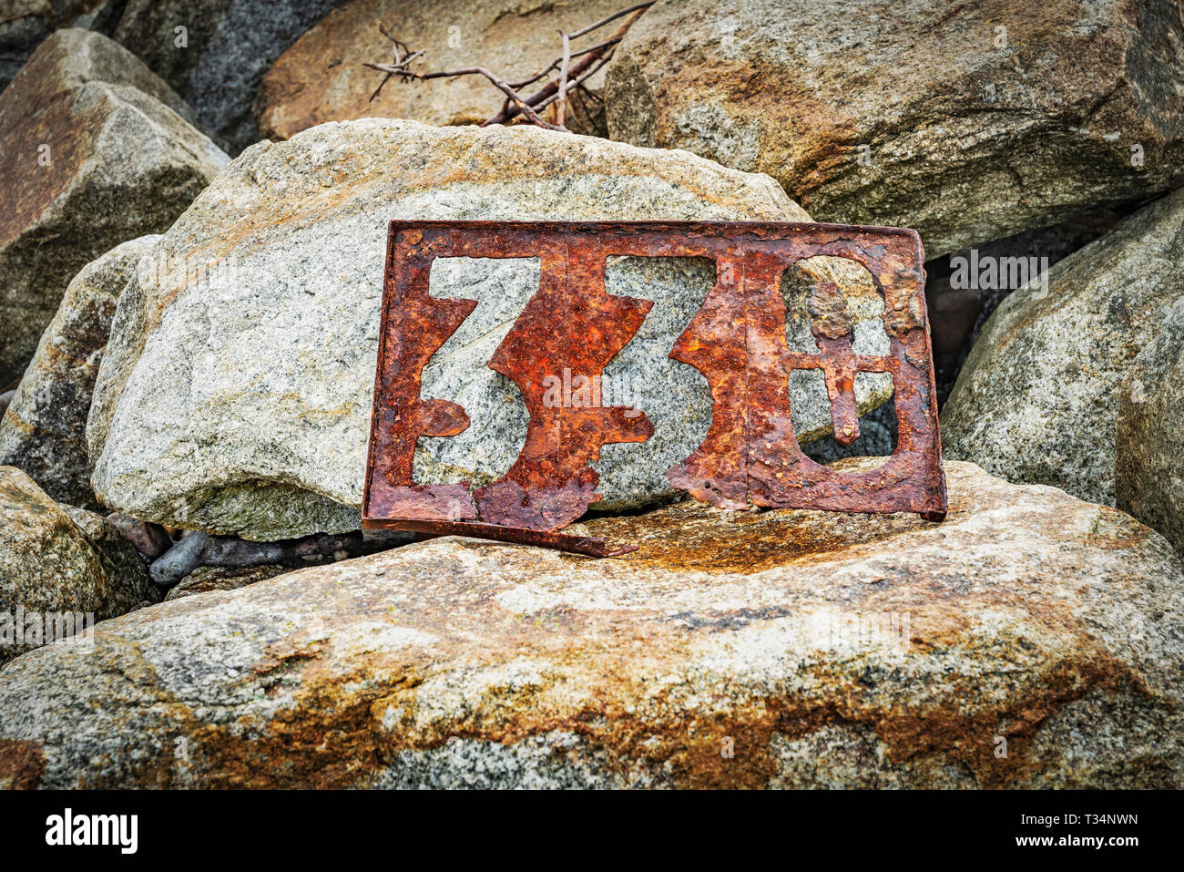A rusted signpost with the number 330 stands on stones. The Sign is located on the Beach of the Baltic Sea in Kolobrzeg,West Pomeranian, Poland, Europ Stock Photo