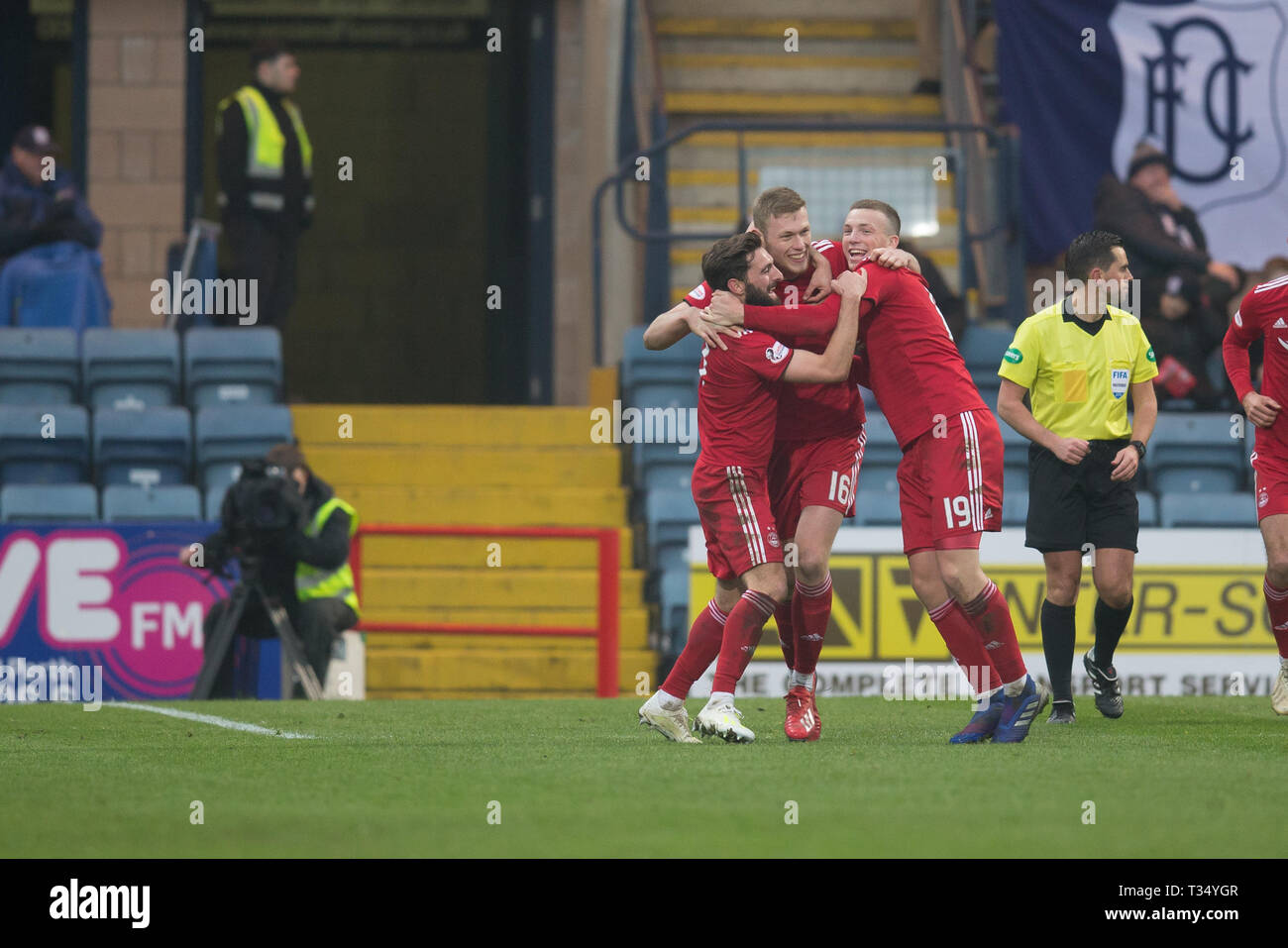 Dens Park, Dundee, UK. 6th Apr, 2019. Ladbrokes Premiership football, Dundee versus Aberdeen; Sam Cosgrove of Aberdeen is congratulated after scoring for 2-0 by Graeme Shinnie and Lewis Ferguson Credit: Action Plus Sports/Alamy Live News - Stock Image