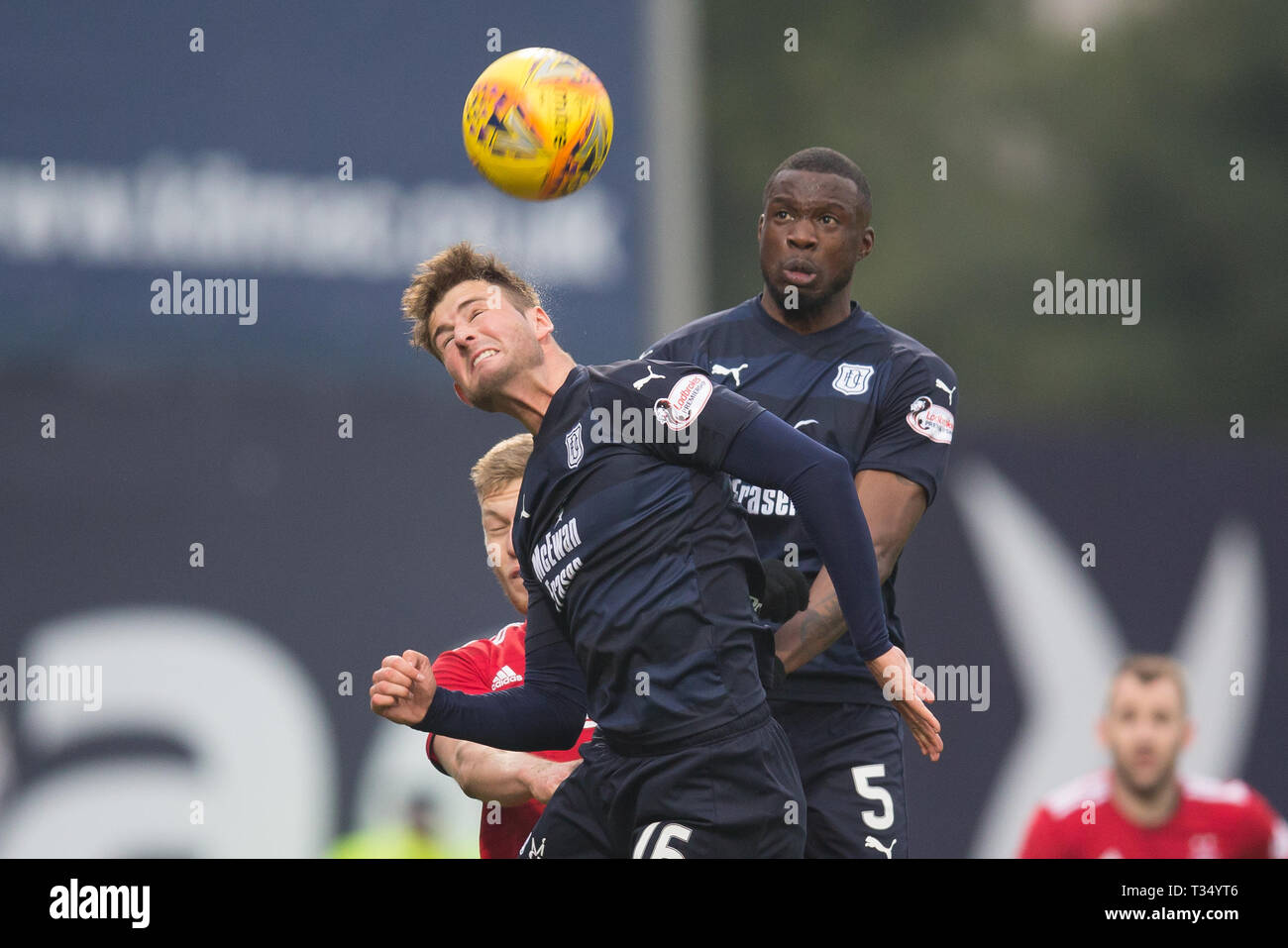 Dens Park, Dundee, UK. 6th Apr, 2019. Ladbrokes Premiership football, Dundee versus Aberdeen; Ethan Robson and Genserix Kusunga of Dundee competes in the air with Sam Cosgrove of Aberdeen Credit: Action Plus Sports/Alamy Live News - Stock Image