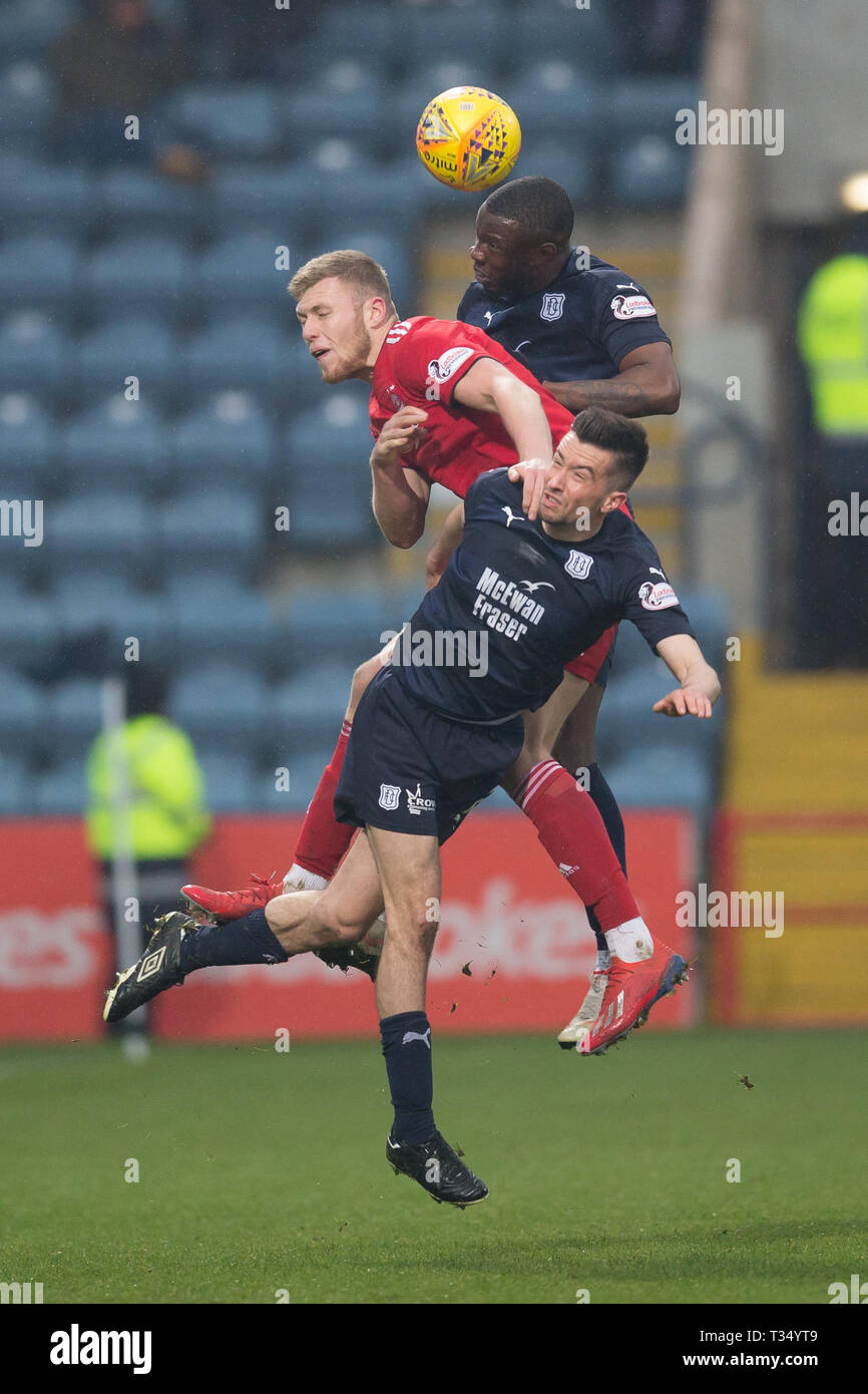 Dens Park, Dundee, UK. 6th Apr, 2019. Ladbrokes Premiership football, Dundee versus Aberdeen; Genserix Kusunga and Cammy Kerr of Dundee competes in the air with Sam Cosgrove of Aberdeen Credit: Action Plus Sports/Alamy Live News - Stock Image