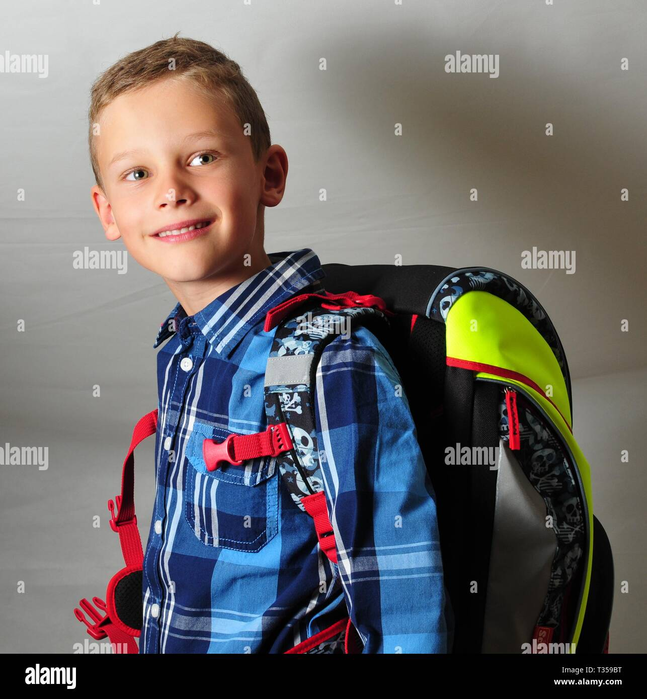 smart boy with checked shirt and schoolbag first grader shines into the camera - Stock Image
