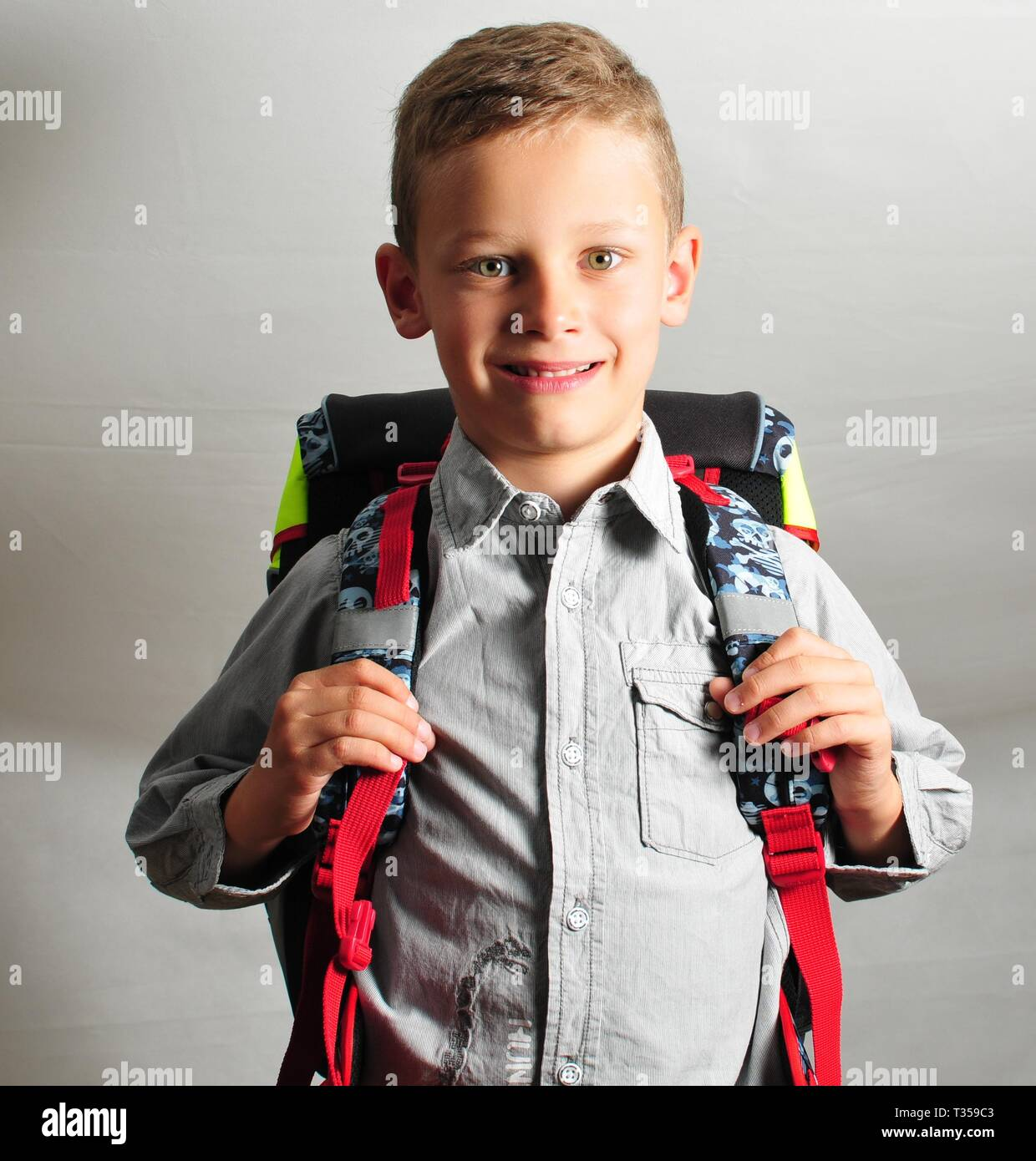 fresh smiling young boy with schoolbag - Stock Image