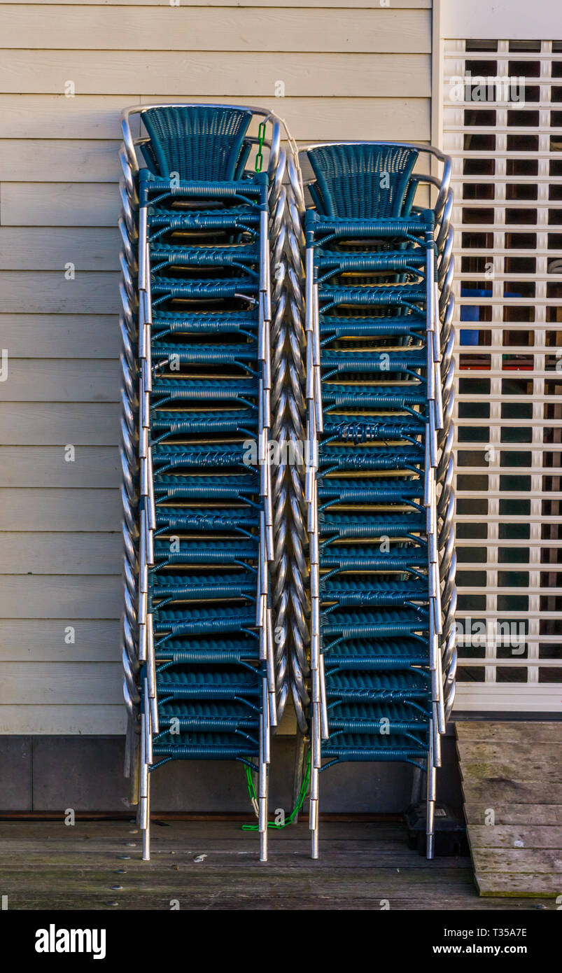 stacked chairs next to a closed rolling shutter, closing time in the catering industry - Stock Image