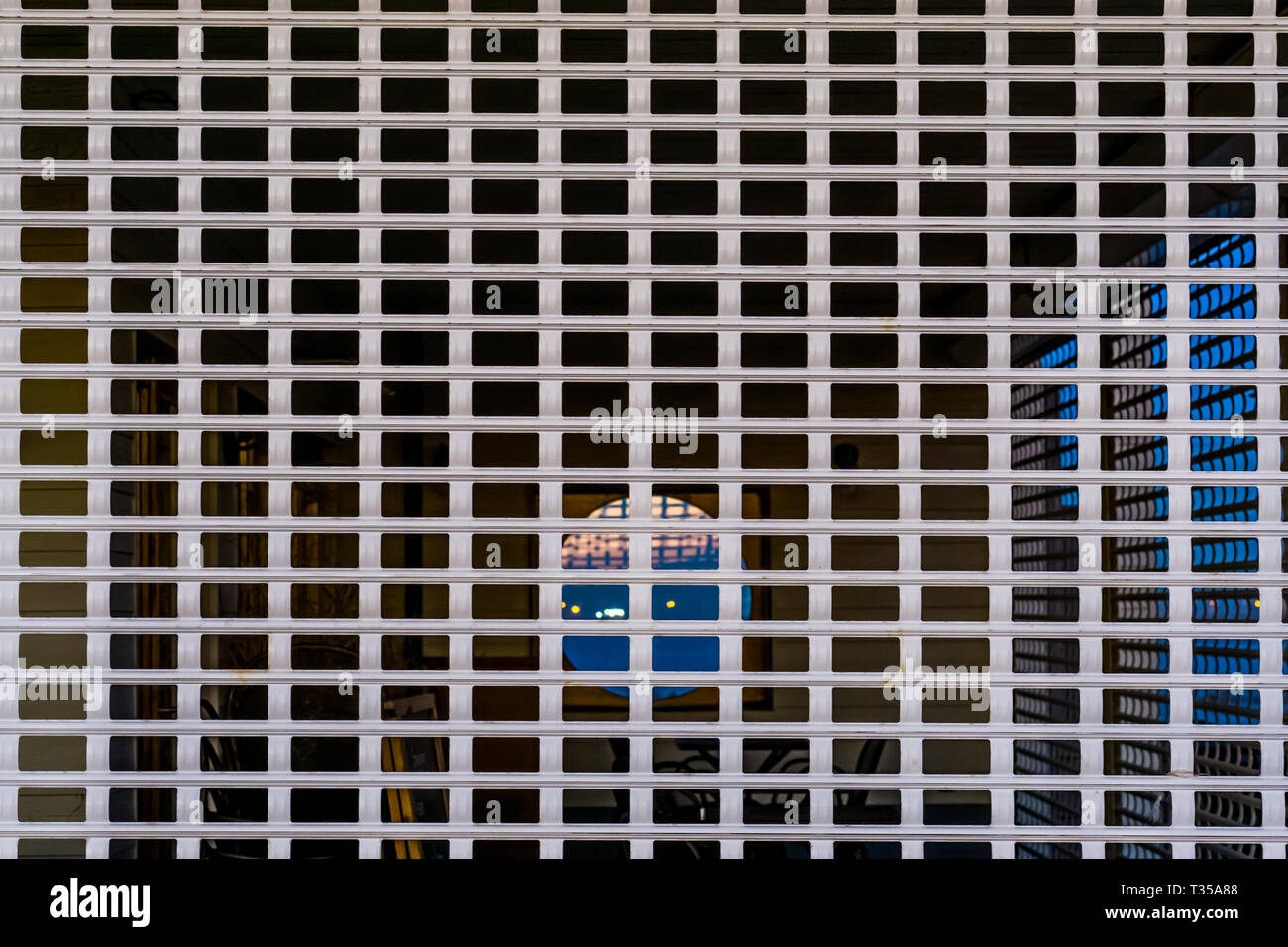 pattern of a closed shutter with holes you can see through, security system for the catering industry, closing time background - Stock Image