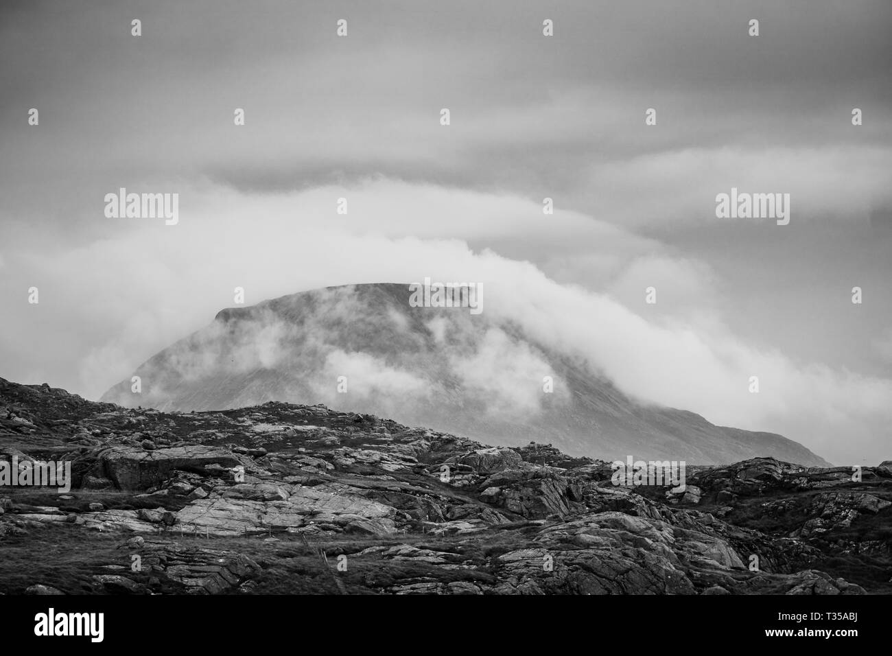 Sheathed in mist and fog, the mountain Ben Arkle, or just Arkle, is seen here as viewed from Blairmore, Sutherland, northern Scotland. - Stock Image