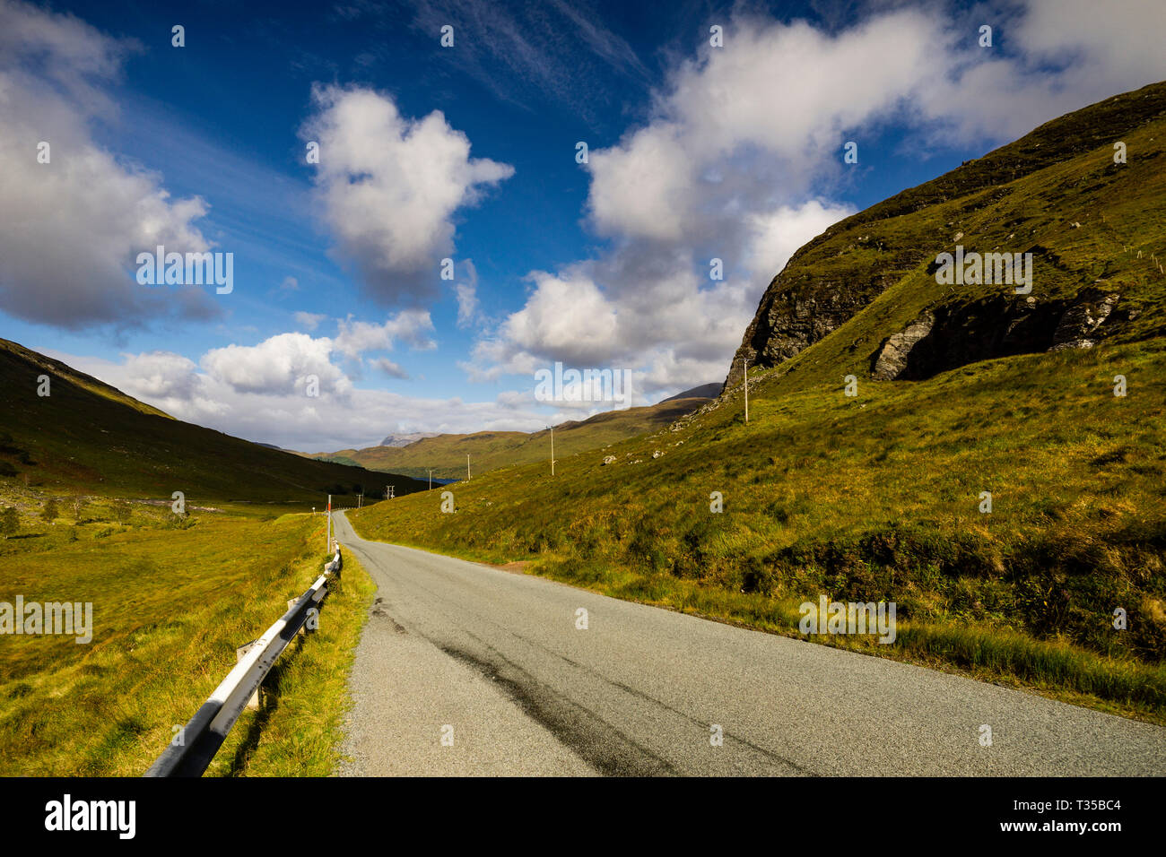A single track road approaches Loch More on a sunny day in the Scottish Highlands. - Stock Image