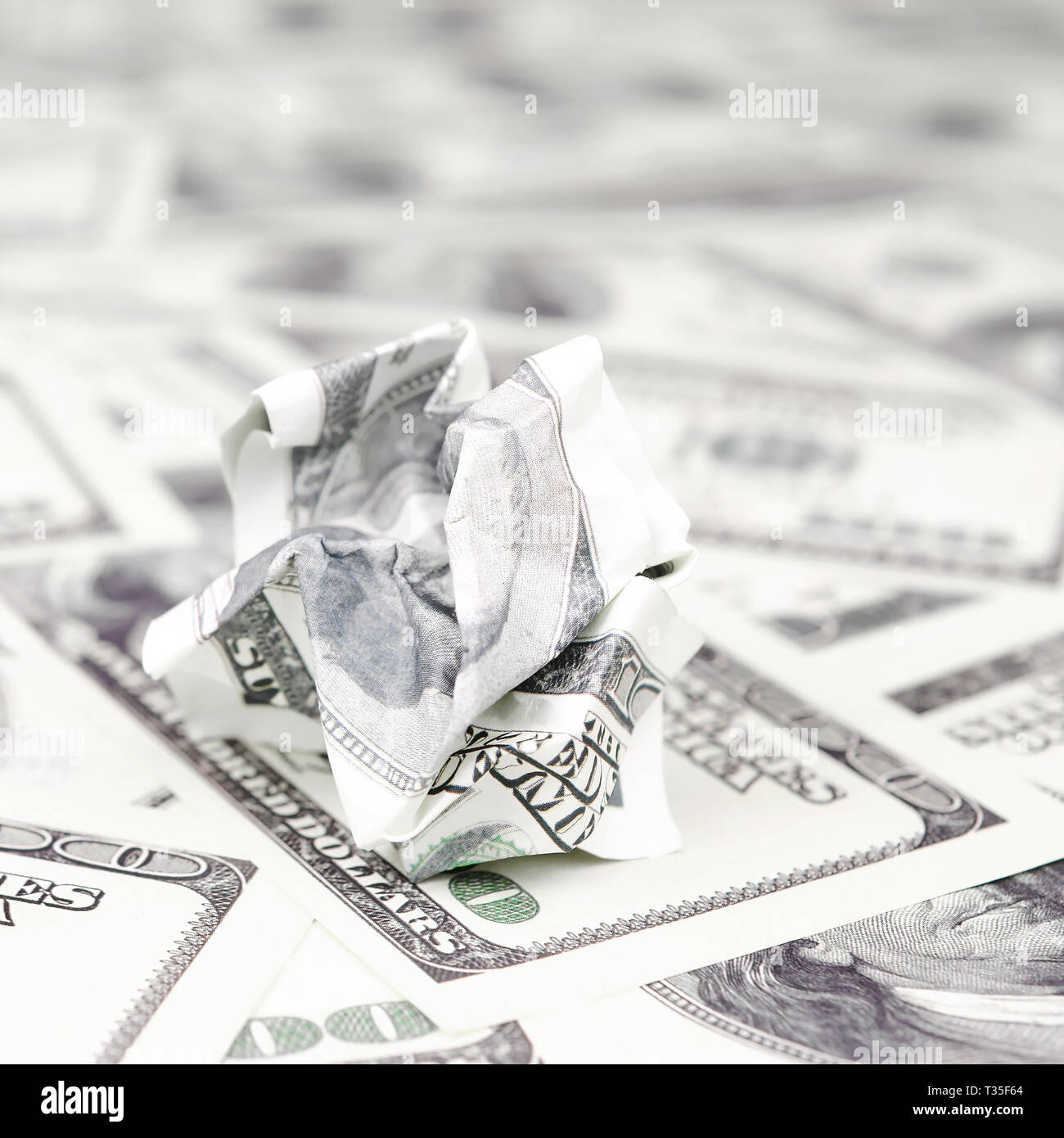 Crumpled dollar bill of the United States lies on the set of smooth money bills. Concept of unreasonable waste of money Stock Photo
