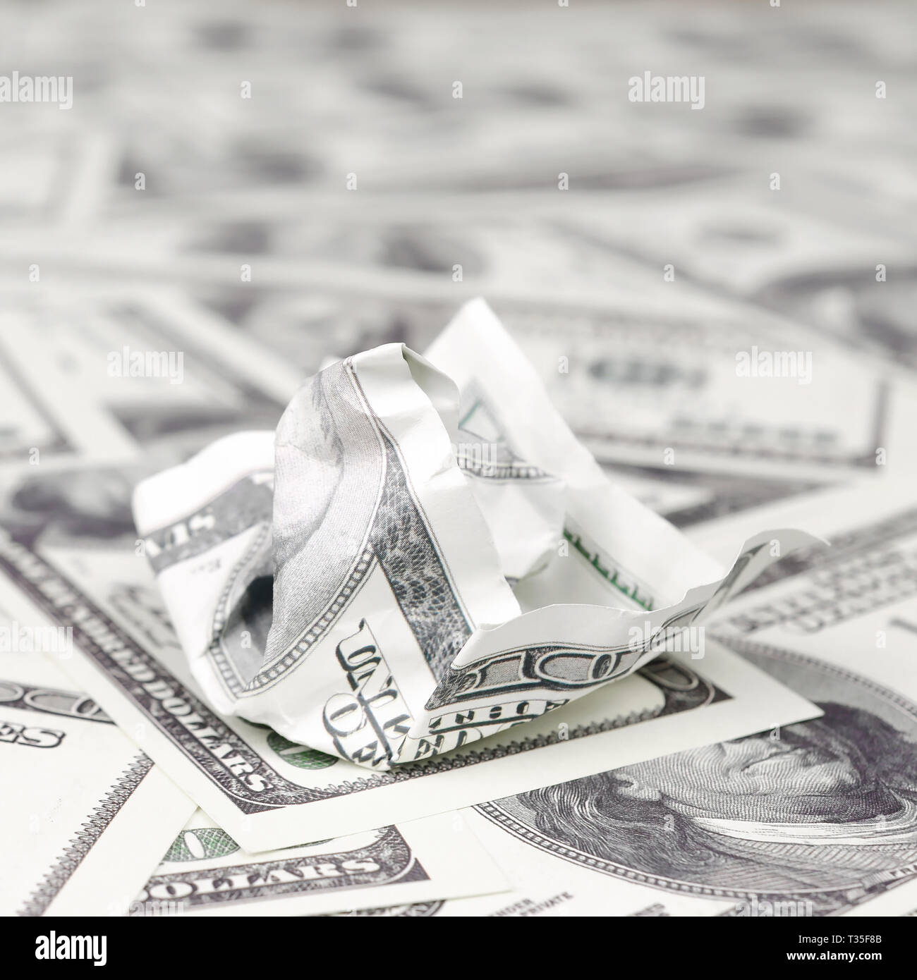 Crumpled dollar bill of the United States lies on the set of smooth money bills. Concept of unreasonable waste of money - Stock Image