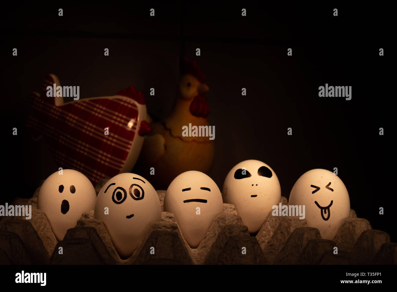 Several eggs with funny faces. They are watched over by two chickens out of focus. Conceptual image - Stock Image
