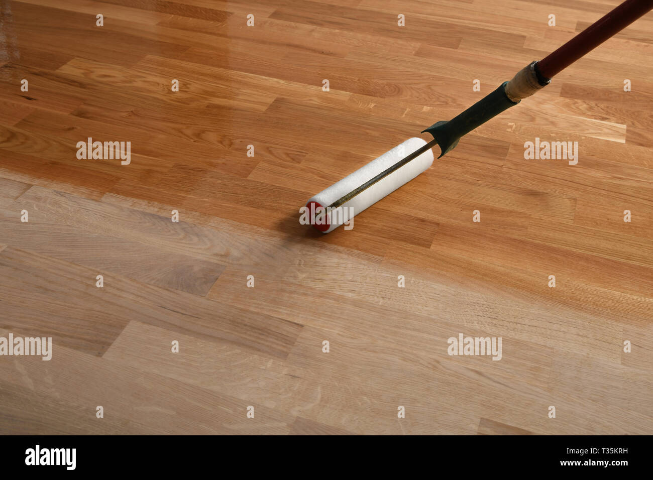 Lacquering Wood Floors Worker Uses A Roller To Coating Floors