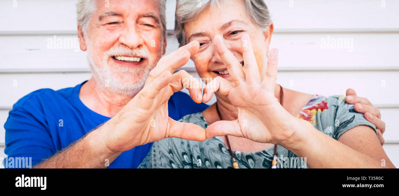 70 year old senior couple playing forming heart with hands. Happiness and joy together forever concept for old people man and woman - romantic and rom - Stock Image