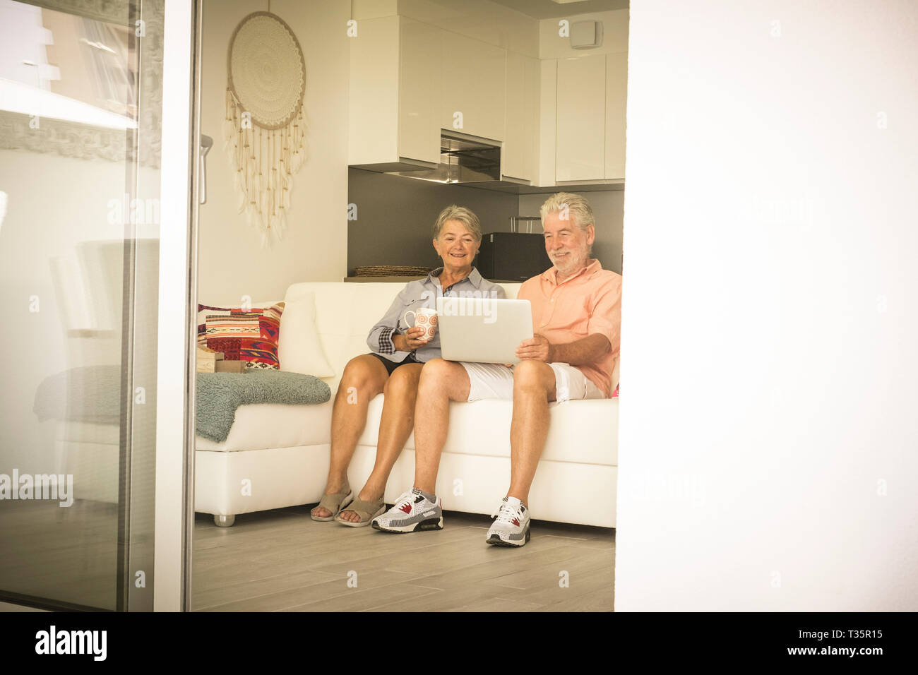 Elderly lifestyle with caucasian old aged mature couple at home sitting on the white sofa and enjoying technology laptop together in relax - senior pe Stock Photo