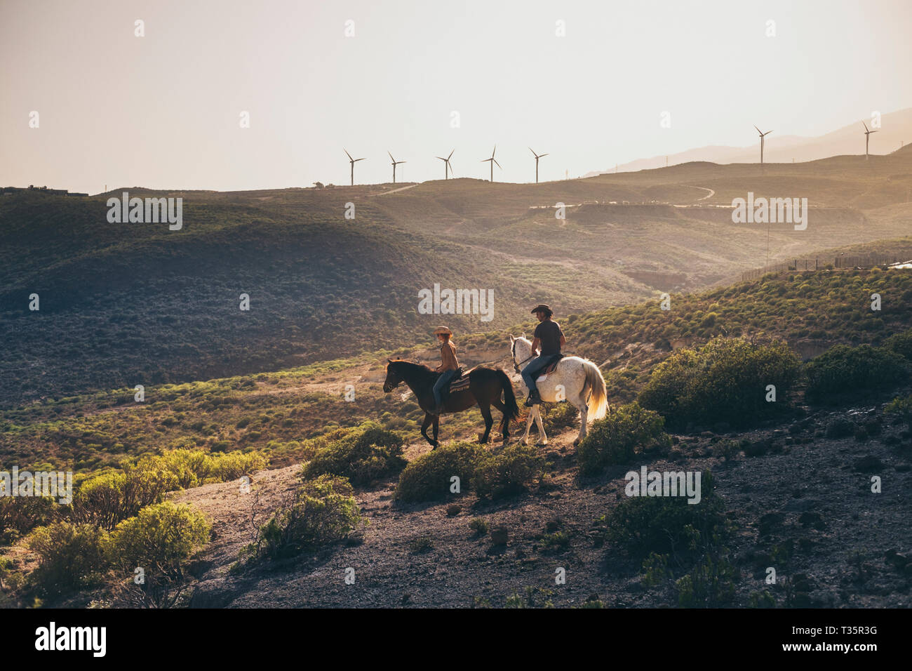 Beautiful landscape on mountain with windmills in background and couple of people riding horse for excursion on alternative cowboy farm lifestyle - su Stock Photo