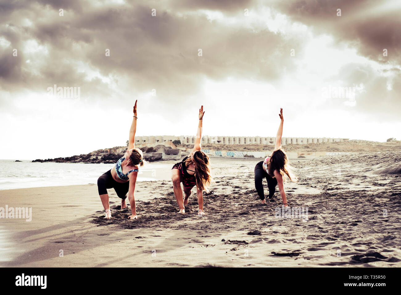 Pilates balance position three young active women at the beach doing sport fitness activity together under a dramatic cloudy sky - scenic image of peo Stock Photo