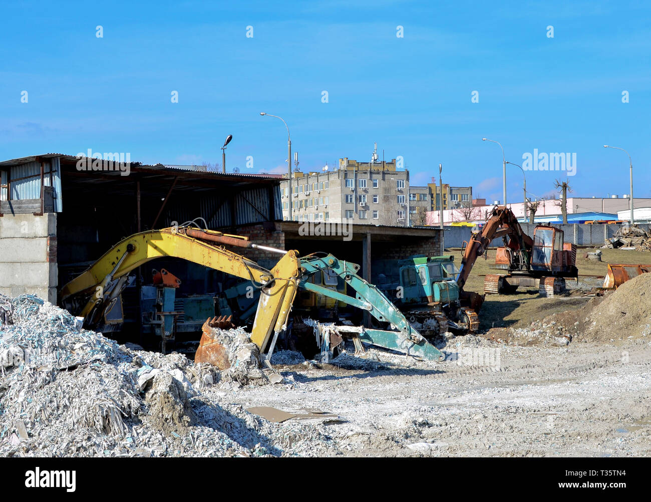 Old rusty abandoned construction excavators with a bucket on the ground in a hangar at a construction site - Stock Image