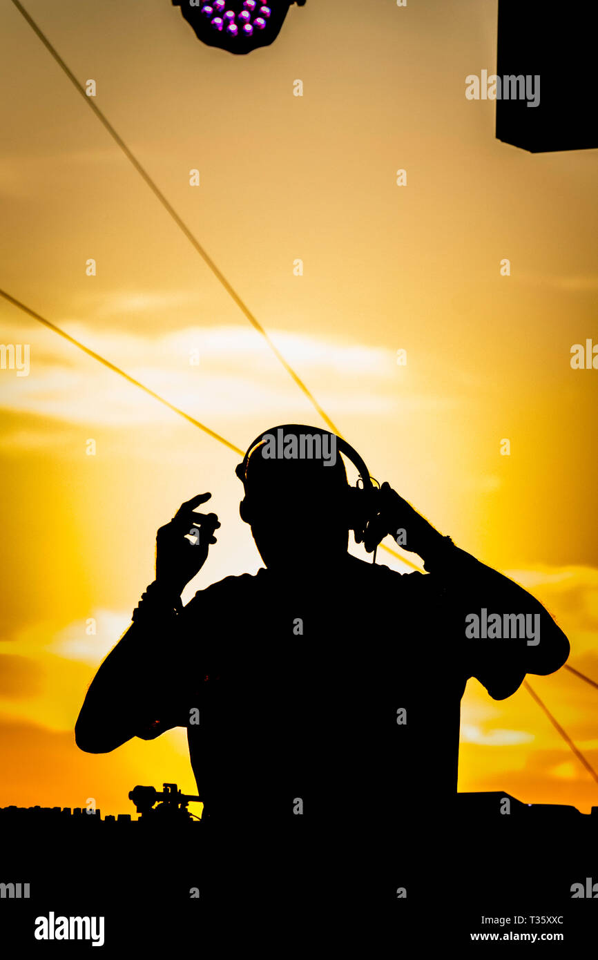 club DJ silhouetted against evening sunset on rooftop event at fiche la belle de mai - Stock Image
