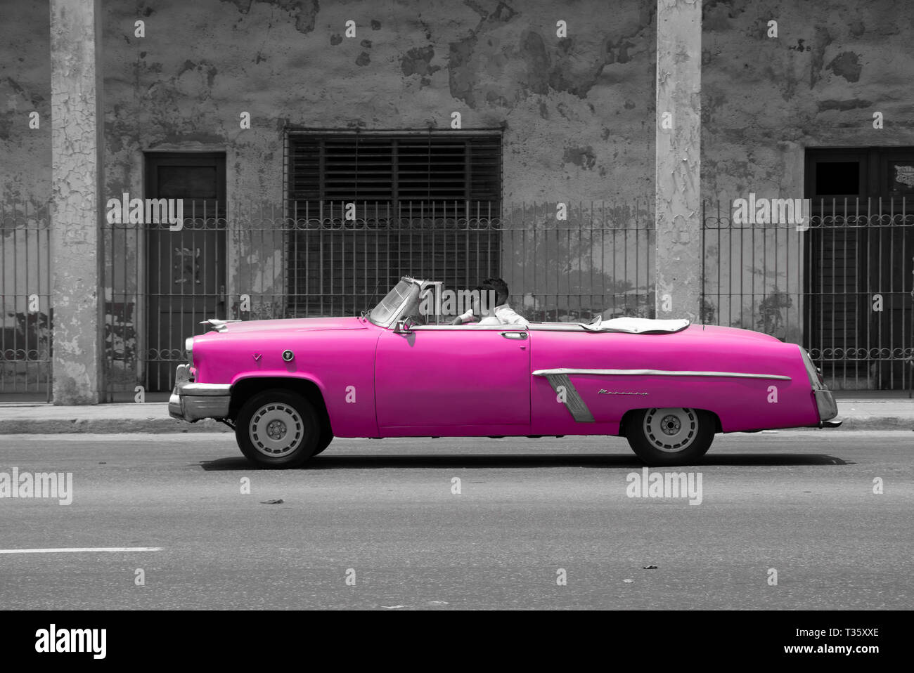 side view of two men in pink classic 1950s American car against a black and white background of a street scene in Havana Cuba Stock Photo