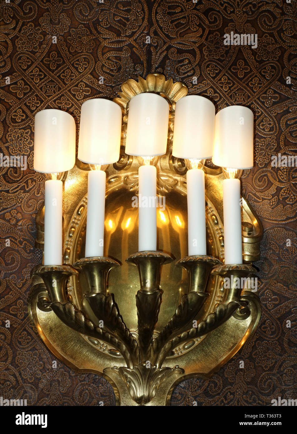 Brass wall sconce on tooled leather wall in Biltmore House, Asheville, North Carolina, US, 2017. - Stock Image