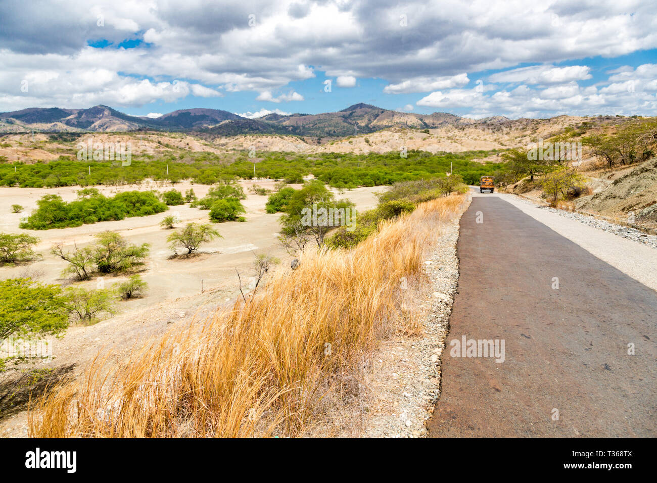 Asphalt road from Dili to Baucau with an orange truck in a distance. Dry savanna. Rural landscape, nature of East Timor or Timor-Leste, near Baucau, V Stock Photo