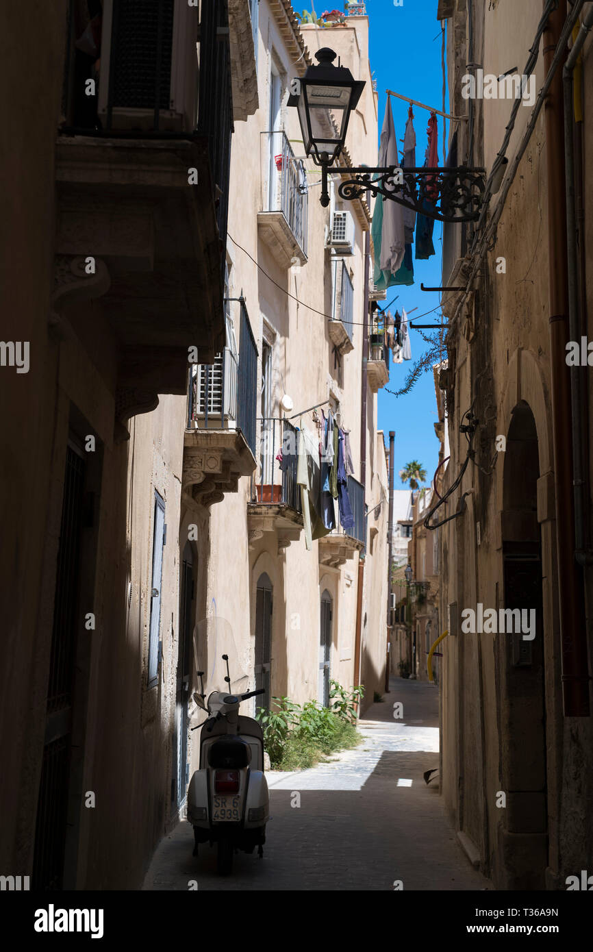 Motorscooter, balconies, lantern and laundry in street scene in alleyway in Greek Streets by via Della Giudecca, Ortigia, Syracuse, Sicily Stock Photo