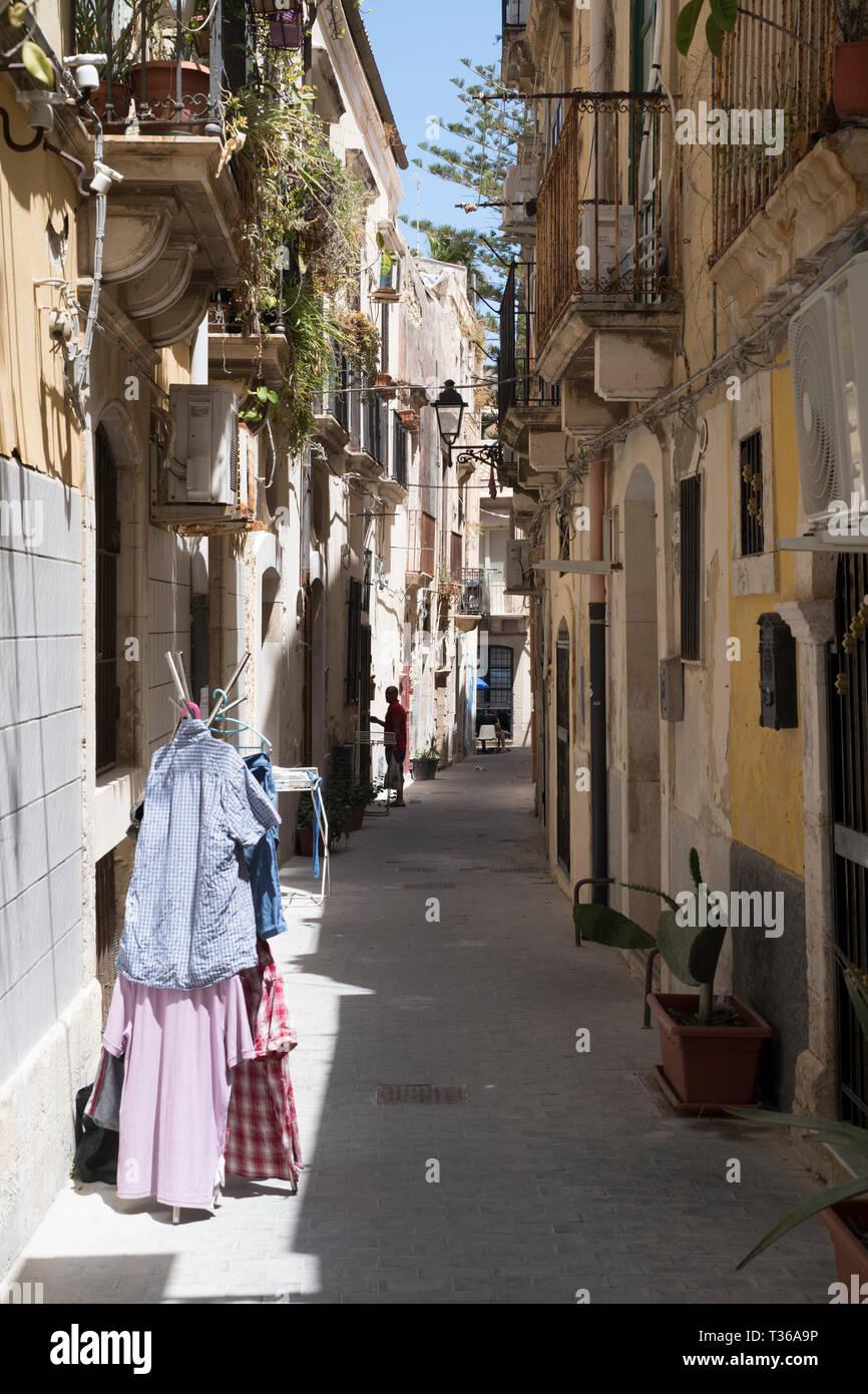 Balconies, lanterns and laundry in street scene in alleyway in Greek Streets by via Della Giudecca, Ortigia, Syracuse, Sicily - Stock Image
