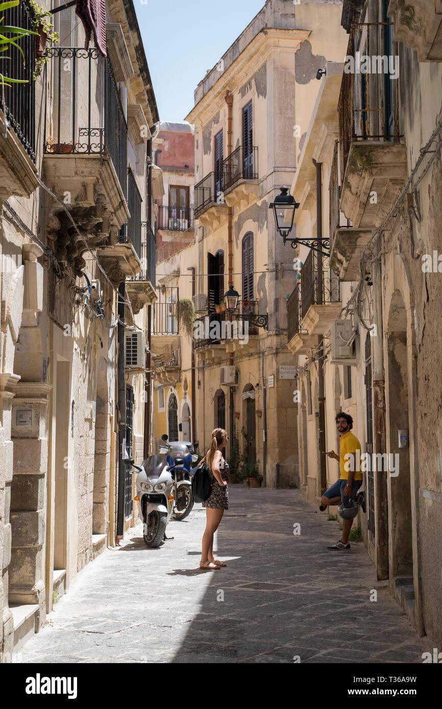Locals in street scene in alleyway in Greek Streets by via Della Giudecca, Ortigia, Syracuse, Sicily - Stock Image