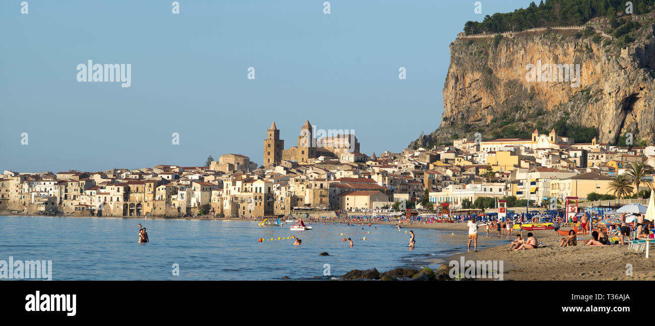 Tourists in coastal town of Cefalu with Baroque style architecture in Northern Sicily, Italy - Stock Image