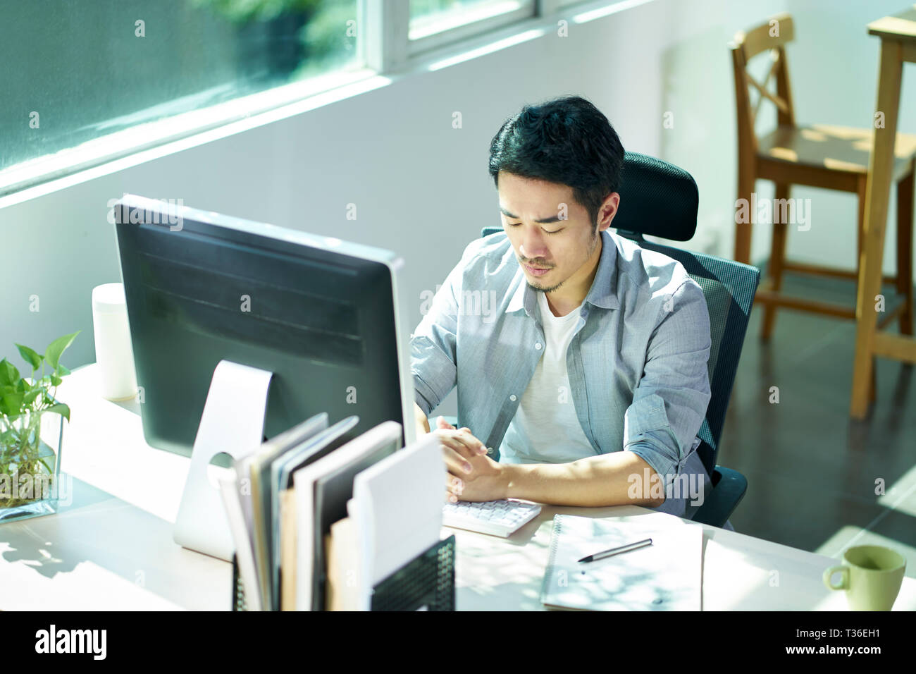 young asian business man entrepreneur sitting at desk in office contemplating. - Stock Image