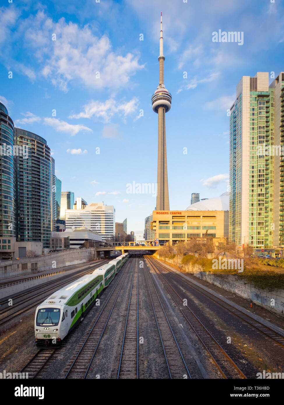 A view of the CN Tower, Rogers Centre (SkyDome), condos, and a GO train leaving downtown Toronto, Ontario, Canada. - Stock Image