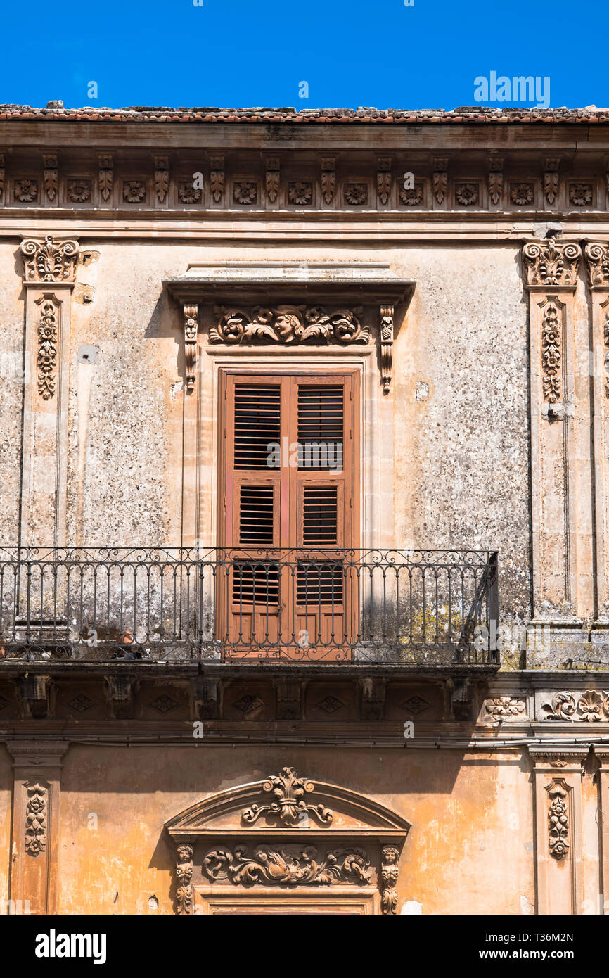 Typical traditional Sicilian architecture balcony, shutters and ornate stonework in Piazza San Giovanni in Ragusa Ibla, Sicily Stock Photo