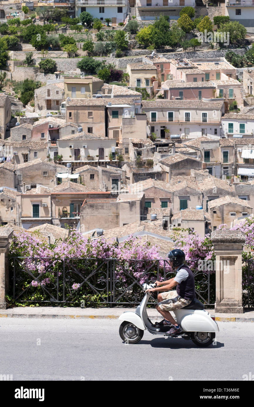 Man riding motorscooter in hill city of Modica Alta looking towards Modica Bassa, Sicily, Italy Stock Photo