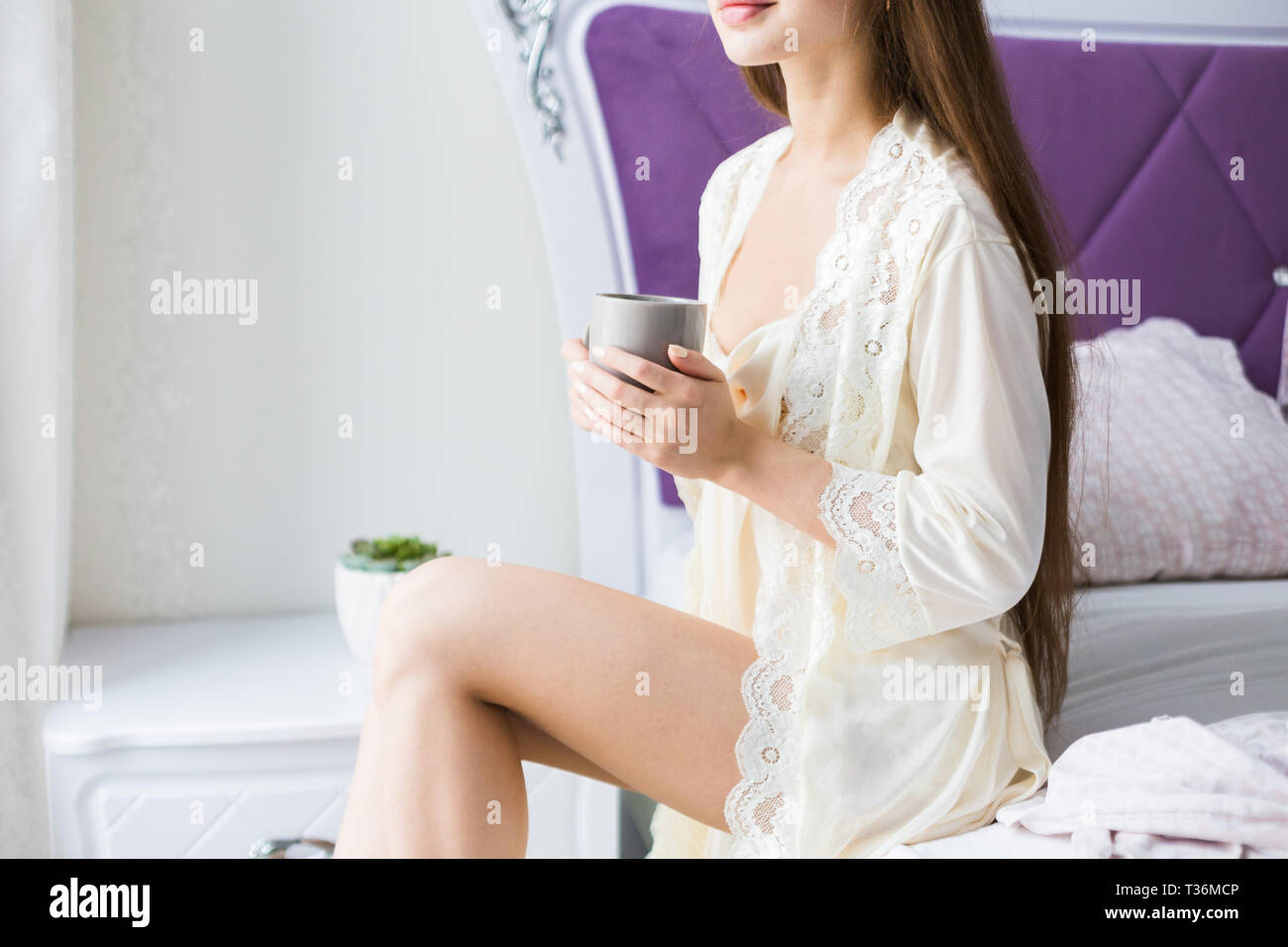 Attractive young girl in nightwear sits on the edge of the bed by the window with a cup of coffee, - Stock Image