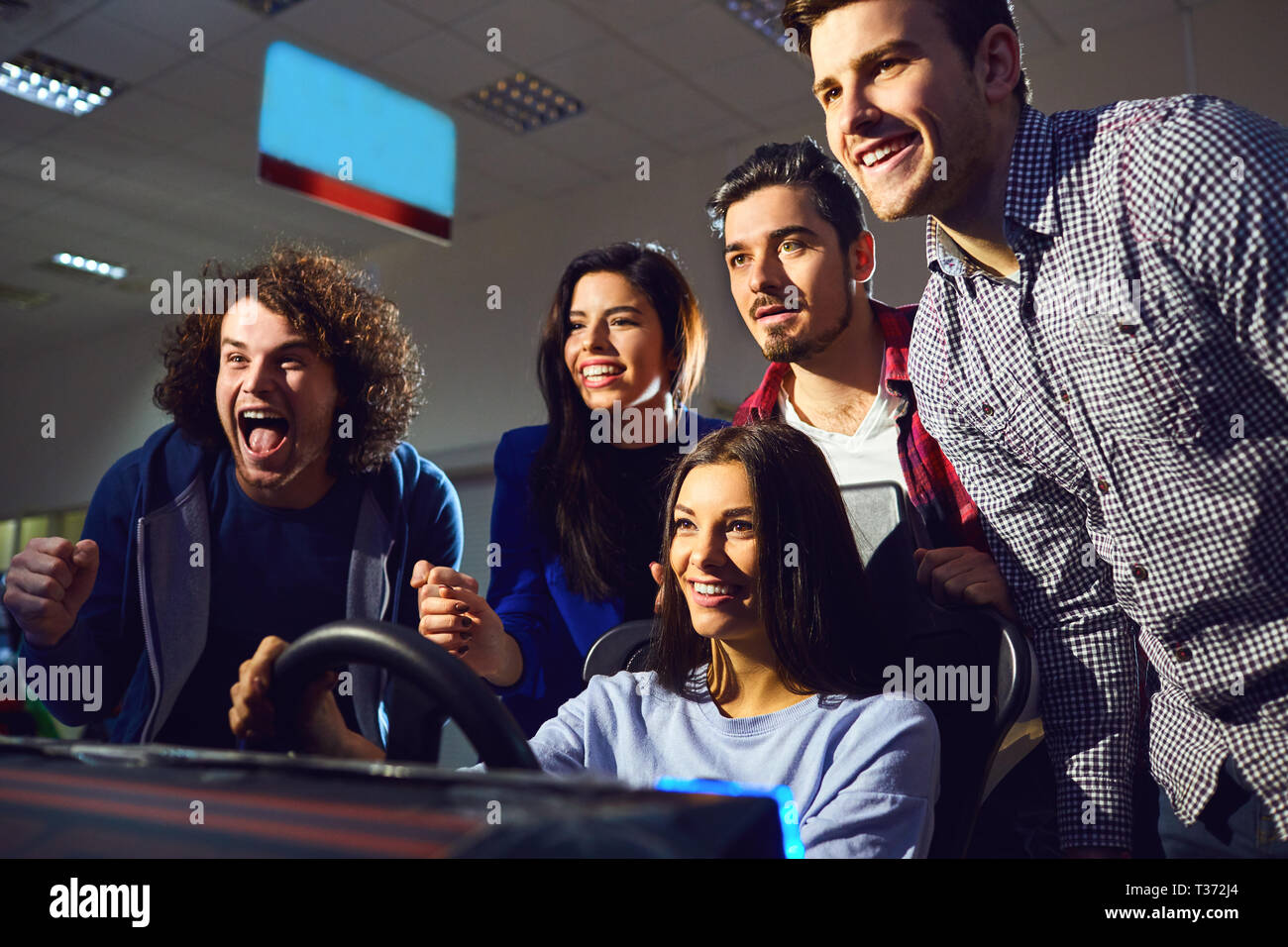 A group of friends playing arcade machine. - Stock Image