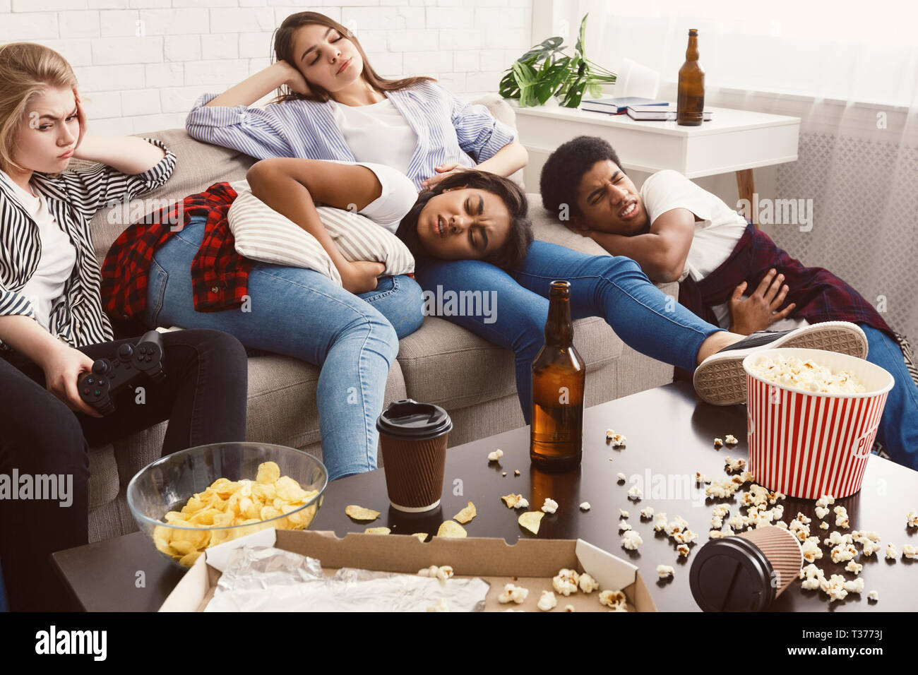 Friends suffering from stomachache and headache in messy room - Stock Image