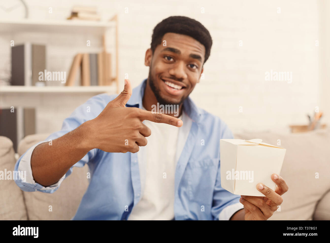 I love it. Emotional african american guy recommend chinese fast food in paper box, free space for trade mark - Stock Image