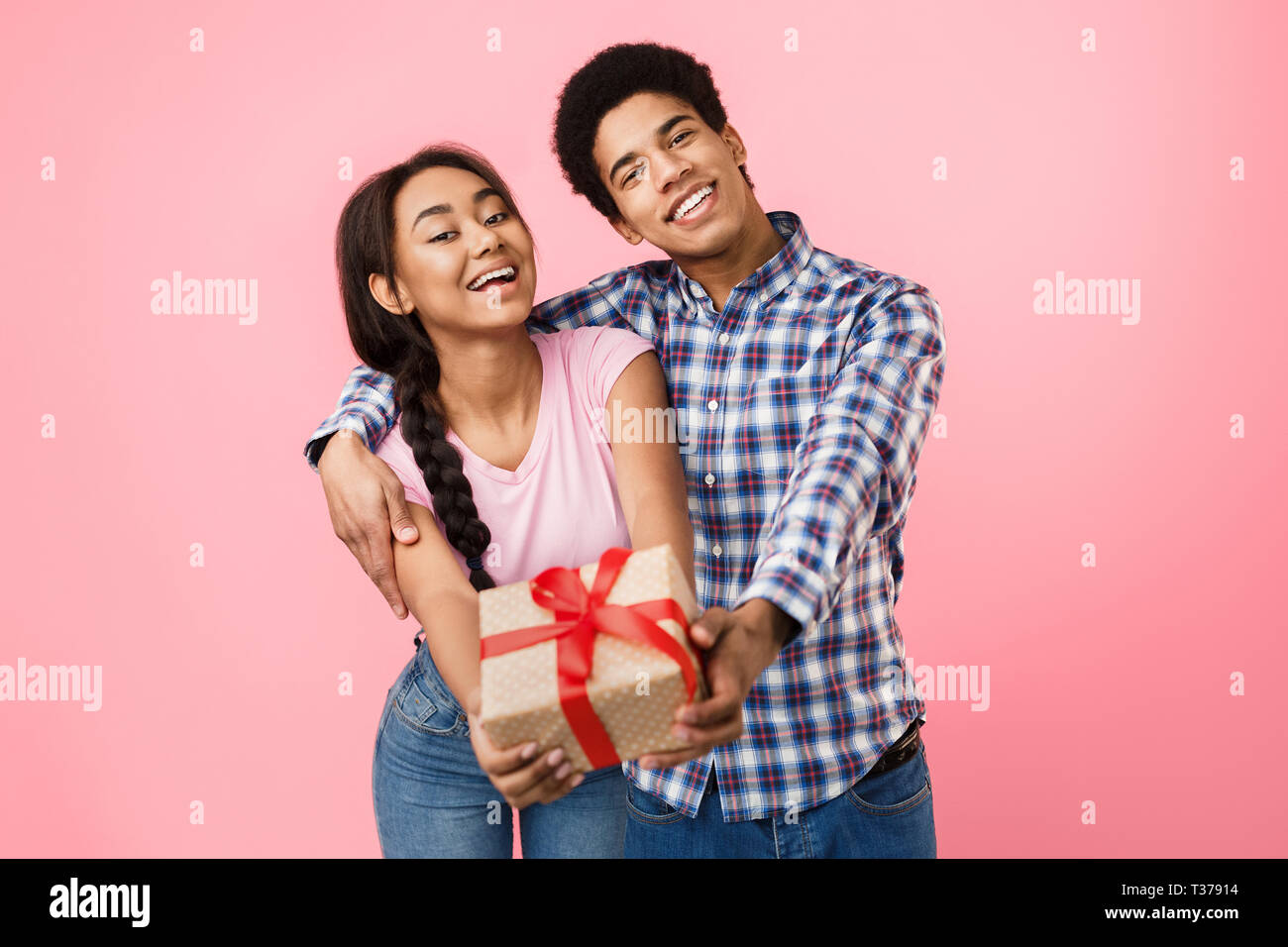 Teenage couple rejoicing, stretching present box to camera over pink background - Stock Image